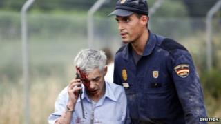 Injured passenger helped away by policeman. 24 July 2013