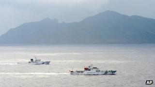 A Japan Coast Guard vessel, left, sails along with a Chinese surveillance ship, right, near disputed islands, rear, called Senkaku in Japan and Diaoyu in China in the East China Sea, 23 April 2013