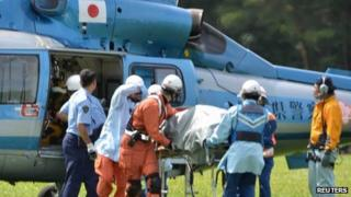 Rescue workers transport an unconscious South Korean hiker on a stretcher from a helicopter in Komagane, Japan, 30 July 2013