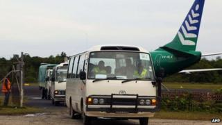 This Australian Government Department of Immigration and Citizenship handout photo taken on 1 August 2013 shows the first group of 40 asylum-seekers arriving in mini-buses shortly after landing on Manus Island, Papua New Guinea, formally bringing into effect the Regional Settlement Arrangement