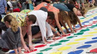 Lots of people playing Twister, with arms and legs crossing over each other