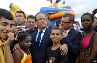French President Francois Hollande (centre) meets people in Clichy-Sous-Bois, near Paris, 31 July
