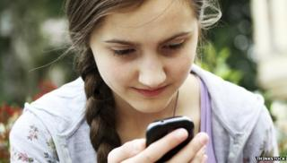 Young girl using mobile - posed by model