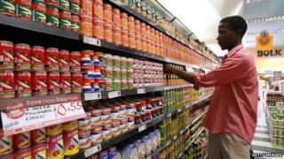 A shop worker arranging cans in a Harare supermarket