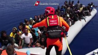 An Italian coast guard talks to African migrants aboard a boat off Lampedusa, 9 August