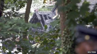 A burnt home is pictured at the site of a plane crash in East Haven