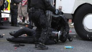 Injured police officer on the ground during loyalist protest in Belfast