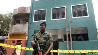 Special Task Force commandos stand guard outside a vandalised mosque in Colombo on 11 August 2013