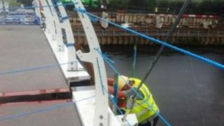 A worker on scaffolding next to the new bridge