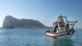 A Spanish fishing boat in the sea, with the Rock of Gibraltar in the background