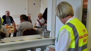 Salvation Army volunteers provide tea and toast for residents