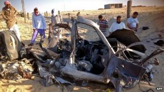 Egyptians gather near a wreckage of a car in El-Arish. Photo: July 2013