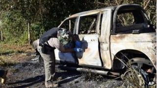 A burnt-out police vehicle is inspected by a officer in San Pedro, north of Paraguay, 18 August