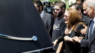 Sahar Bahadi, centre, mother of Sammy Yatim, cries as she follows the hearse carrying the casket of her son at his funeral in Toronto, 1 August 2013