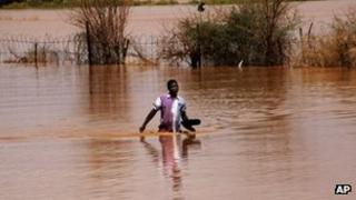 A Sudanese man wades through floodwaters in Khartoum. Photo: 3 August 2013