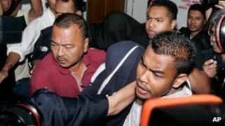 Former policemen Azilah Hadri, center covered with blue cloth, and Sirul Azhar Umar, back center covered with black cloth, are escorted by police as they leave a court in Shah Alam, outside Kuala Lumpur, Malaysia, on 9 April 2009