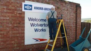 A workman changing the sign at the Railcare site