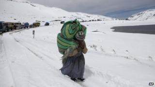 A woman walks along a snowy road on the outskirts of La Paz, Bolivia on 25 August 2013