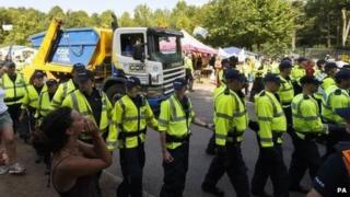 Police escort a lorry arriving at the site