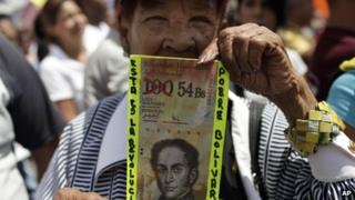 A man holds up a fake Bolivar bill at a protest march in February 2013