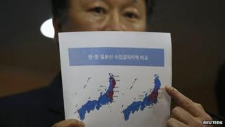 Vice-Minister of Maritime Affairs and Fisheries Son Jae-hak points at a document showing Japanese prefectures with import bans (in red) imposed by South Korea (L) and China (R) respectively at a news conference in Seoul on 6 September 2013
