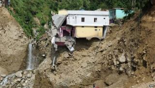 A damaged house perches on the mountainside alongside the Mandakini river at Silli, in the flood affected area of northern Uttarakhand state on July 1, 2013