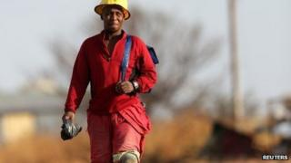 A miner walks as he returns from work outside Driefontein Gold Mine,70 km (43 miles) west of Johannesburg, 4 September 2013