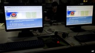 A computer user sits near displays with a message from the Chinese police on the proper use of the internet at an internet cafe in Beijing, China, Monday, 19 August 2013