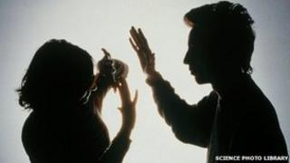 Silhouette of a woman protecting herself from a blow from her partner