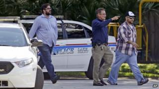 George Zimmerman, far right, is escorted by a police officer, centre, in Lake Mary, Florida after a domestic incident