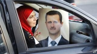 Syrian woman with a poster of president assad