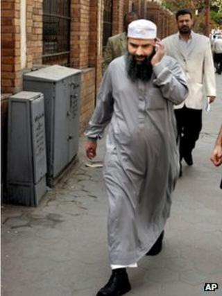 Egyptian cleric Osama Hassan Mustafa Nasr talks on his mobile as he walks at a Cairo street on 11 April 2007.