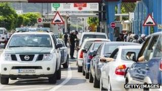 Members of the Guardia Civil check cars as motorists queue to cross the border between Spain and Gibraltar in La Linea de la Concepcion on August 22, 2013