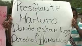 "A protesters holds up a sign saying ""President Maduro: Where are the human rights?"""