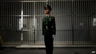 A paramilitary guard stands before the bars of a main gate to the No.1 Detention Centre during a government guided tour in Beijing on 25 October 2012