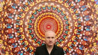 "Artist Damien Hirst with his work ""I Am Become Death, Shatterer of Worlds 2006"", on display at Tate Modern art gallery in 2012"