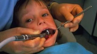 Child at dentist having tooth drilled to treat tooth decay
