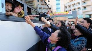 File photo (1 November 2010) shows North Koreans (on bus) waving to their South Korean relatives as they bid farewell following their three-day separated family reunion meeting at the Mount Kumgang resort on the North's south-eastern coast