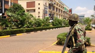 A soldier moves to take up a position outside an upscale shopping mall, seen background, in Nairobi, Kenya Saturday 21 September 2013.