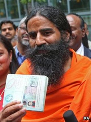 Swami Ramdevji holding up his passport, which has been stamped to show he has been granted a UK visa
