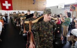 At an official visitors' day at a Swiss Army base, veterinary section troops play traditional cow-bells