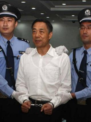 "Bo Xilai (C) wearing a pair of handcuffs as he stands in a courtroom in Jinan, east China""s Shandong province"