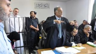 Fathi Ashram (second left) stands inside the Gaza City courtroom during his trial