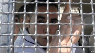 Tunisian rapper Ahmed Ben Ahmed, known as Klay BBJ, gestures behind the bars of a police vehicle as he leaves Hammamet court, Tunisia - 26 September 2013