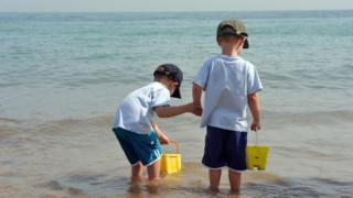 Two children with buckets paddling in the sea