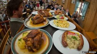 A waiter carries meat-laden plates