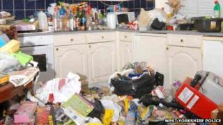 The kitchen in Amanda Hutton's house, with rubbish on the floor and several drink bottles