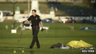Police officer collects a belt at the scene where a man set himself on fire on the National Mall in Washington DC, 4 October 2013