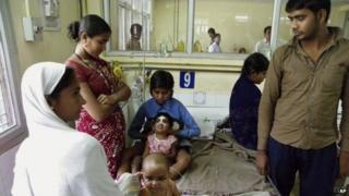 In this Tuesday, April 2, 2013 photo, an Indian child in a pink shirt with a white bandage on her face undergoes treatment for encephalitis at a hospital in Gorakhpur in Uttar Pradesh state, India.
