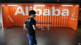 Employee walks past Alibaba sign